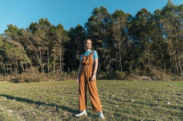 Long shot woman in overall facing sun Free Photo