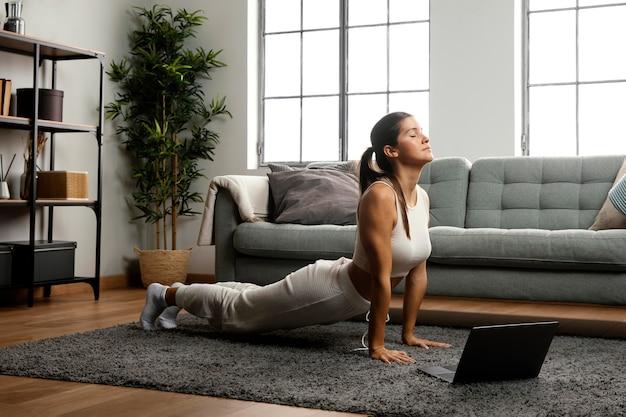 Colpo lungo della donna che pratica yoga Foto Gratuite
