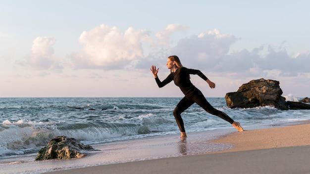 Длинный выстрел женщина работает на пляже Бесплатные Фотографии