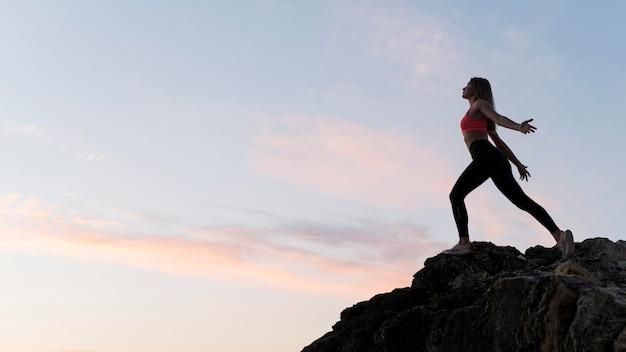 Colpo lungo donna in abiti sportivi in piedi su una costa con copia spazio Foto Gratuite