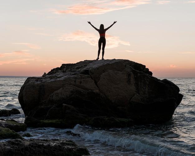 Длинный выстрел женщина, стоящая на большой скале в океане Бесплатные Фотографии