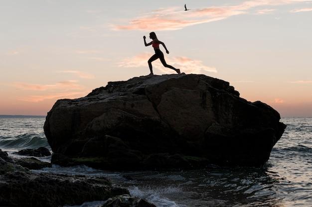 Colpo lungo donna in piedi in una posizione sportiva su una roccia Foto Gratuite