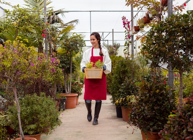 Long shot woman wearing gardening clothes and holding basket in greenhouse Free Photo