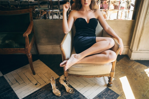 Long skinny legs barefoot with high heeled sandals shoes, fashion details of elegant beautiful woman sitting in vintage cafe in black velvet dress, rich stylish lady, elegant trend footwear Free Photo