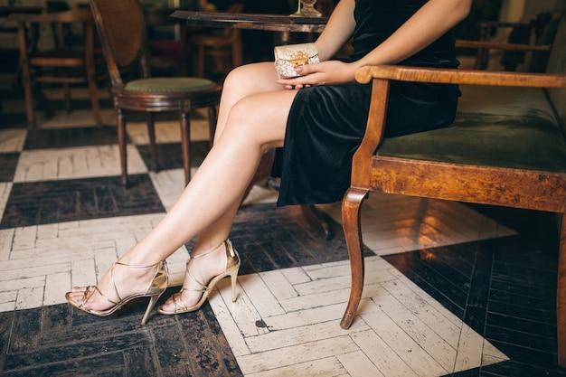 ハイヒールのサンダルの靴を履いている長い細い脚、黒いベルベットのドレスでヴィンテージカフェに座っているエレガントな美しい女性のファッションの詳細、豊かなスタイリッシュな女性、エレガントなトレンドの靴 無料写真