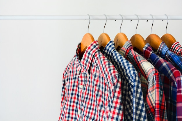 Long sleeve checkered shirt on wooden hanger hang on clothing rack over white background Premium Photo