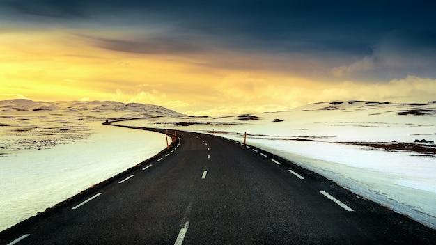 冬の日没時の長い直線道路。 無料写真