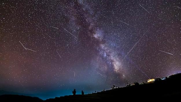 오두막 산 위에 유성우 동안 은하수와 오랜 시간 노출 밤 풍경. 프리미엄 사진