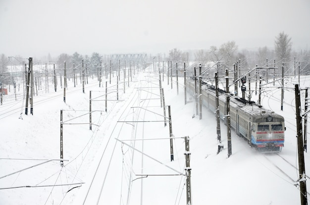 A long train of passenger cars is moving along the railway track. railway landscape in winter after snowfall Premium Photo