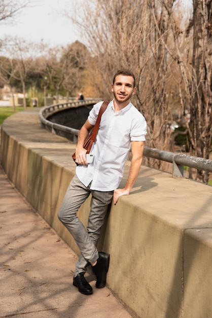 Long view of man posing outside in a white shirt Free Photo