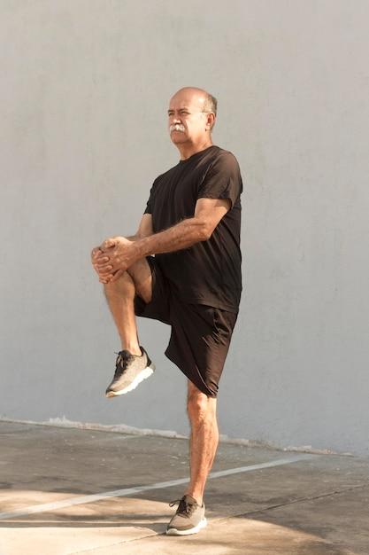Vista lunga dell'uomo che allunga le gambe Foto Gratuite