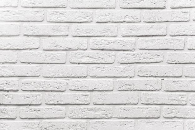 Long white brick wall background. the texture of the old brick painted with white paint Premium Photo
