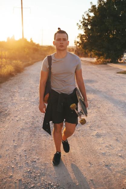 Образ человека с longboard идет по дороге Бесплатные Фотографии