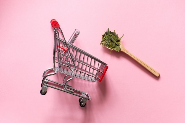Longjing. chinese leaf green tea  in a spoon on a pink background. shopping cart trolley. Premium Photo