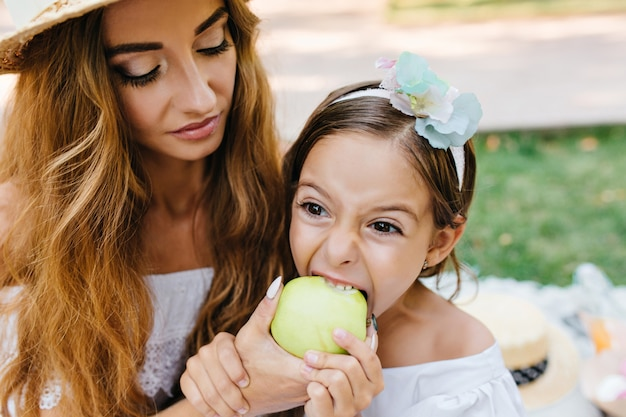 青リンゴとトレンディな化粧を与える娘とlonkg髪の巻き毛の若い女性。公園でのピクニック中に大きな食欲でジューシーな果物を食べるブルネットの少女。 無料写真