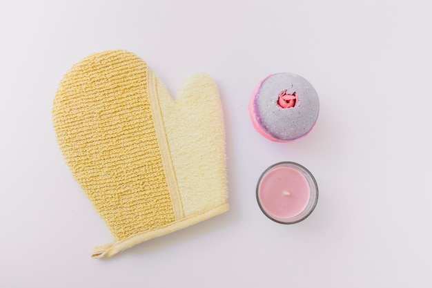 Loofah mitt; bath bomb and candle on white background Free Photo