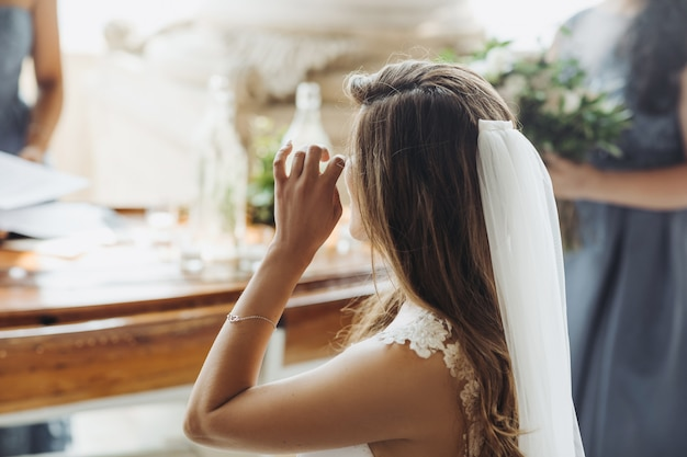 Look from behind at charming bride touching her eyes Free Photo