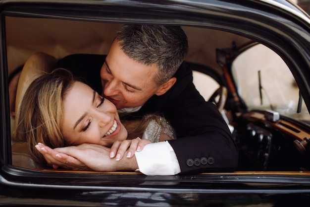 Look from the outside at adorable wedding couple in classy dress Free Photo