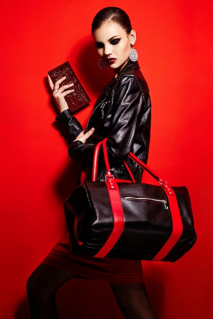 Высокая мода look.glamor крупным планом портрет красивой сексуальной стильной брюнетки кавказской модели молодой женщины в черной куртке с сумкой яркого макияжа, с красными губами, с идеально чистой кожей в студии Бесплатные Фотографии