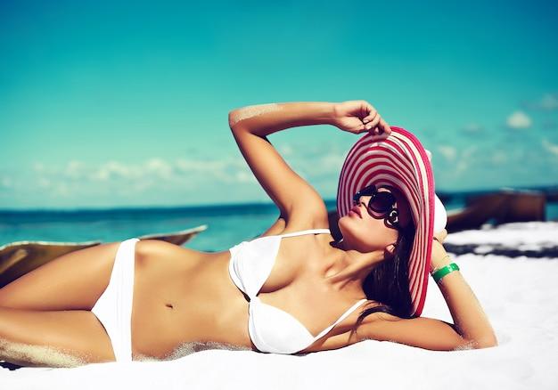 Высокая мода look.glamor - сексуальная загорелая модель, девушка в белом бикини, в разноцветной шляпе от солнца, позирует за синим пляжем, океанская вода Бесплатные Фотографии
