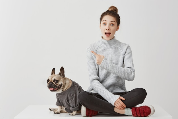 Look there! surprised woman pointing index finger asking for paying attention on something worthy. female model gesturing meaning this is cool in company of dog. lifestyle concept, copy space Free Photo