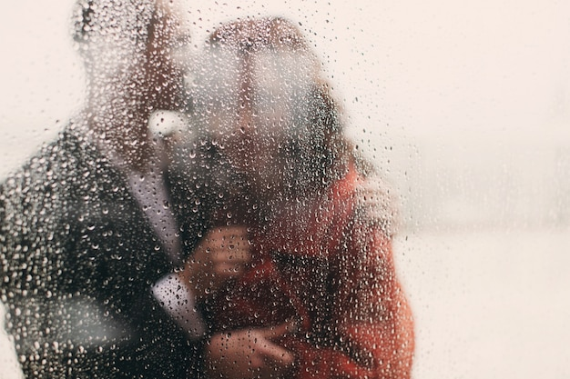 Look throught the wet window at hugging couple Free Photo
