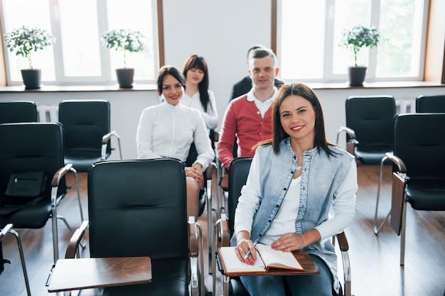 カメラを見てください。昼間の近代的な教室でのビジネス会議での人々のグループ 無料写真
