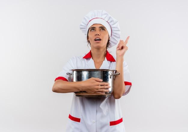 鍋を保持しているシェフの制服を着て、コピースペースのある孤立した白い壁を指している若い女性料理人を考えて見上げる 無料写真