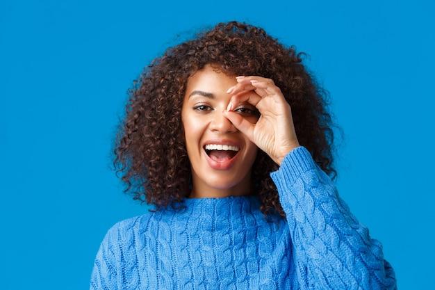 距離を見てください。クローズアップの陽気な魅力的なアフリカ系アメリカ人の女性が何かを探して、素晴らしい休日の割引を見つけ、大丈夫なサインを見て、満足している青い壁を笑っています。 無料写真