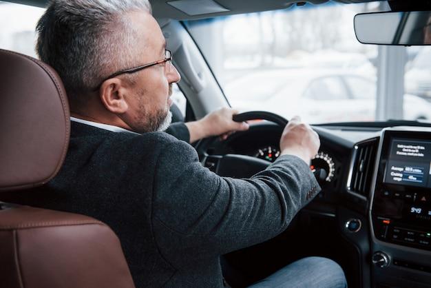 Глядя в переднее зеркало. вид сзади старшего бизнесмена в официальной одежде за рулем современного нового автомобиля Бесплатные Фотографии