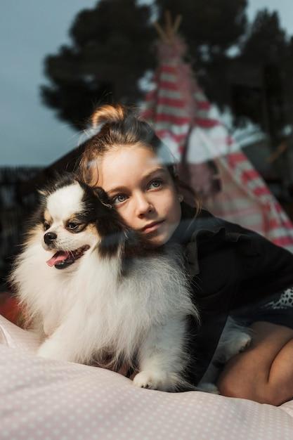 窓の外を見る女の子とふわふわの子犬 無料写真