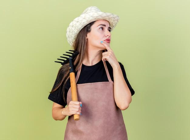 Guardando il lato impressionato bella ragazza giardiniere in uniforme che indossa cappello da giardinaggio tenendo il rastrello Foto Gratuite