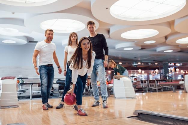 Guardando dritto in avanti. i giovani amici allegri si divertono al bowling durante i fine settimana Foto Gratuite