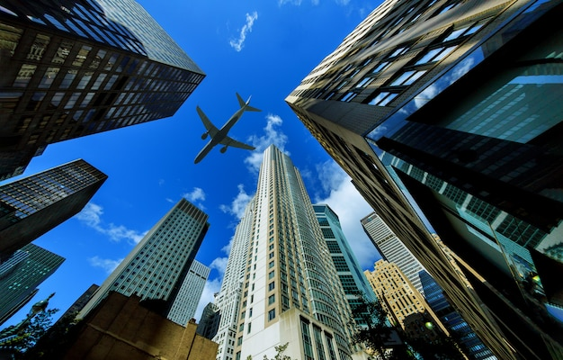 Looking up at new york city skyscrapers in financial district, nyc usa plane flying Premium Photo