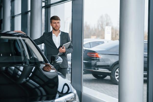 Guarda lontano. uomo d'affari barbuto elegante moderno nel salone dell'automobile Foto Gratuite