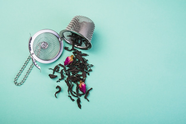 Loose dried tea herbs spilled from the tea strainer against colored backdrop Free Photo