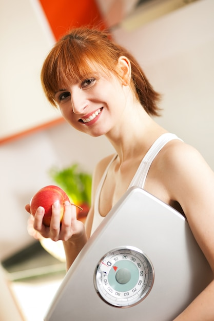 Loosing weight - woman with scale and apple Premium Photo