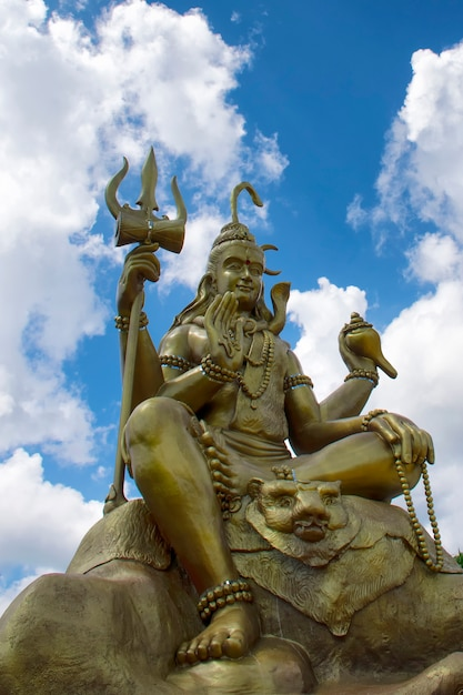 Lord shiva with blue sky in wat chom tham at mea on in chiang mai, thailand Premium Photo
