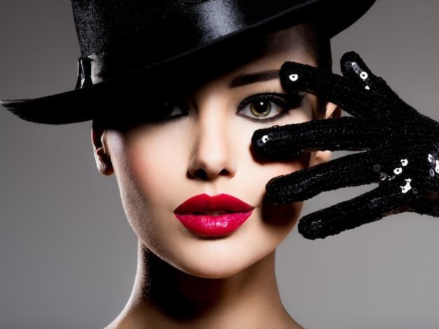 검은 모자에있는 여자와 빨간 입술 포즈와 장갑의 сlose-up 초상화 무료 사진