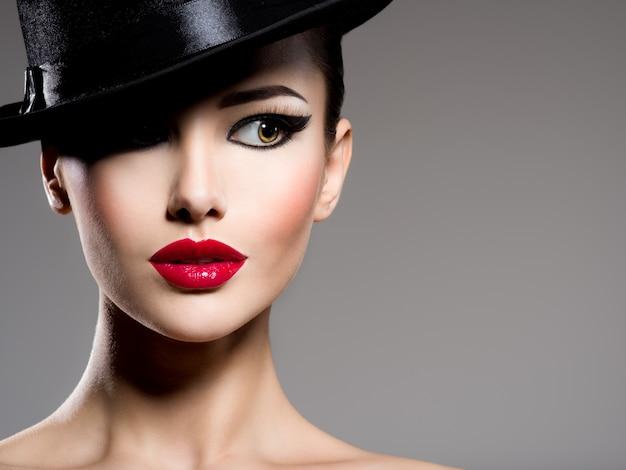 Крупным планом портрет женщины в черной шляпе с красными губами позирует Бесплатные Фотографии