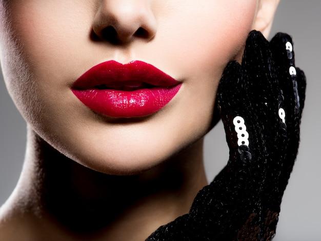 뺨에 빨간 립스틱과 검은 장갑을 낀 여성 입술을 잃어 버리십시오. 무료 사진