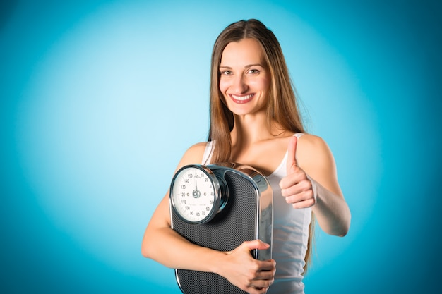 Losing weight, young woman with measuring scale Premium Photo