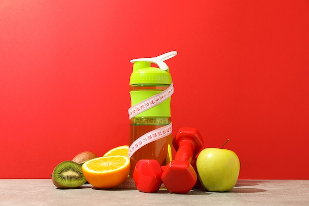 Аксессуары для похудения на сером столе на красном фоне Premium Фотографии