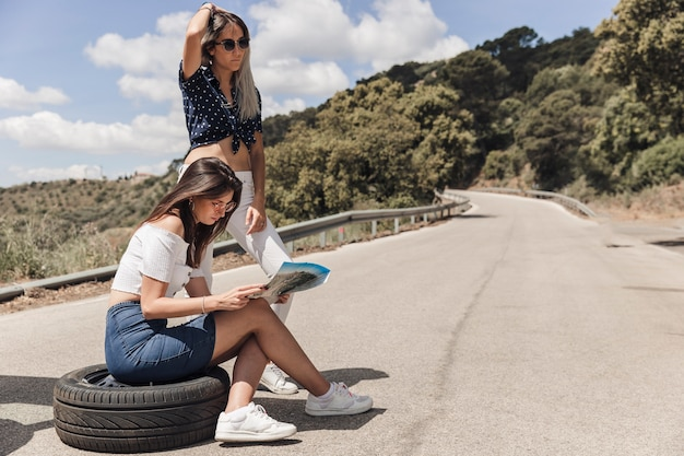 Lost woman sitting on tire with her friend looking at map Free Photo