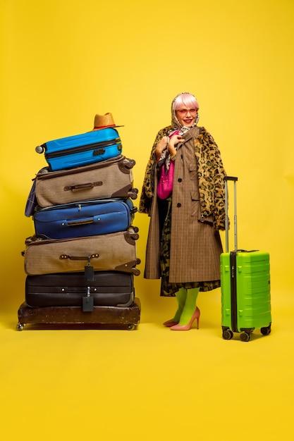 Un sacco di vestiti per viaggiare. ritratto di donna caucasica su sfondo giallo. Foto Gratuite