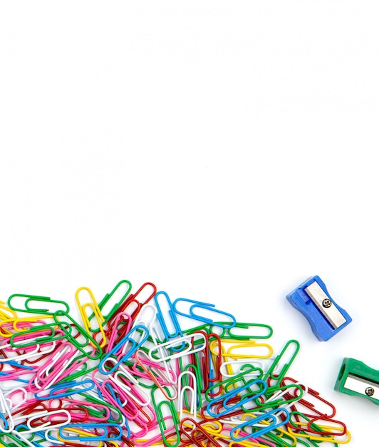 A lot of colored paper clips and pencil sharpeners on a white background. top view and copy space. Premium Photo