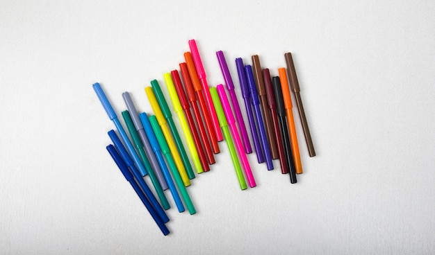 A lot of colored pencils, markers, pens, white background, row markers colored yellow, blue, red. Premium Photo