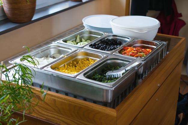 Lotto di diverse verdure tritate in contenitori di metallo Foto Gratuite