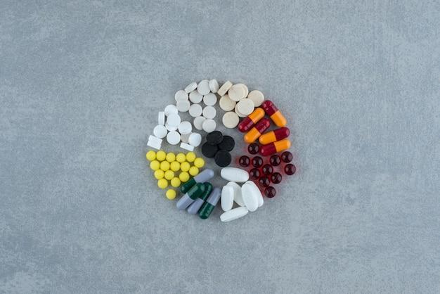 Molte pillole colorate mediche sulla superficie grigia Foto Gratuite
