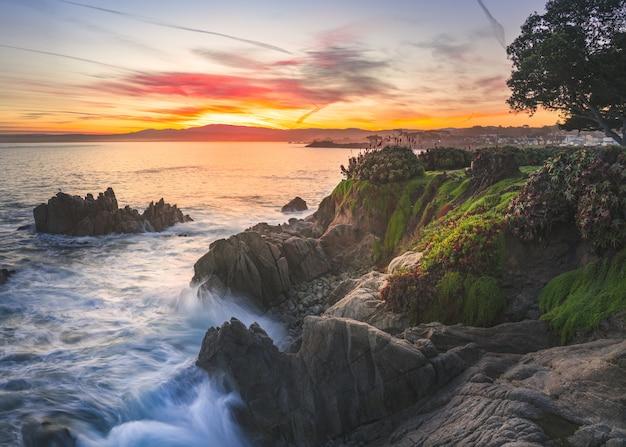 Множество скальных образований, покрытых мхом, у моря под закатным небом Бесплатные Фотографии